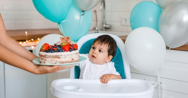 Little baby boy sitting in high chair in white kitchen and tasting first year cake with fruits from mother hands on background with balloons.