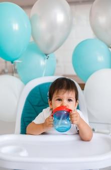 Маленький мальчик сидит в синем стульчике у себя дома на белой кухне и пить воду из чашки поилки на фоне с воздушными шарами.