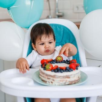 작은 아기 소년 흰색 부엌에서 높은 의자에 앉아 풍선 배경에 과일과 함께 첫해 케이크를 시음.