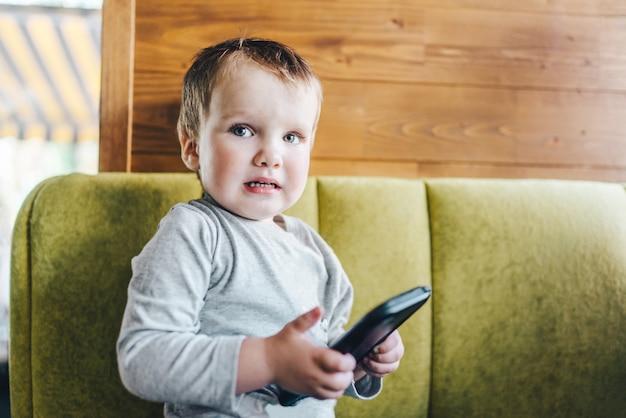 Маленький мальчик сидит на диване с мобильным телефоном в руках, выглядит шокированным