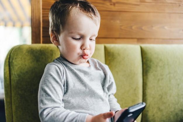 携帯電話を手にソファに座っている小さな男の子は、それを使用して完全に集中しました