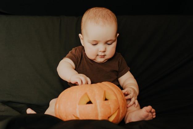 Little baby boy sitting with halloween pumpkin jack