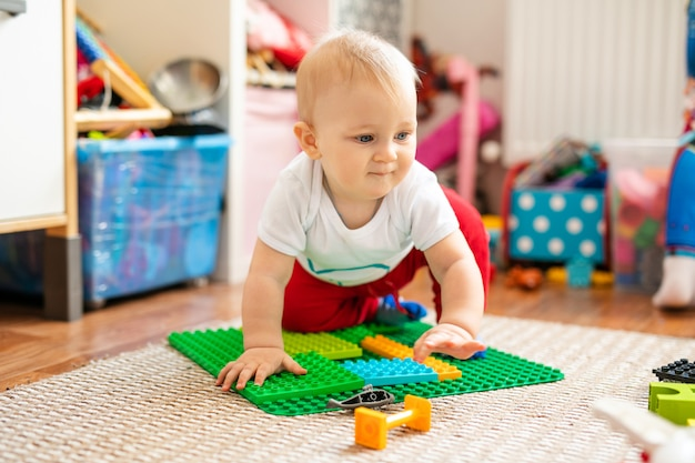 Little baby boy in white t-shirt with a toys on the floor at home