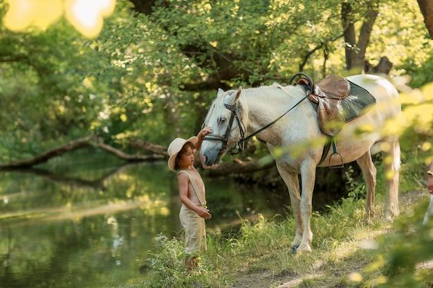 Маленький мальчик с вьющимися волосами, одетый как хоббит, играя с лошадью в лесу летом