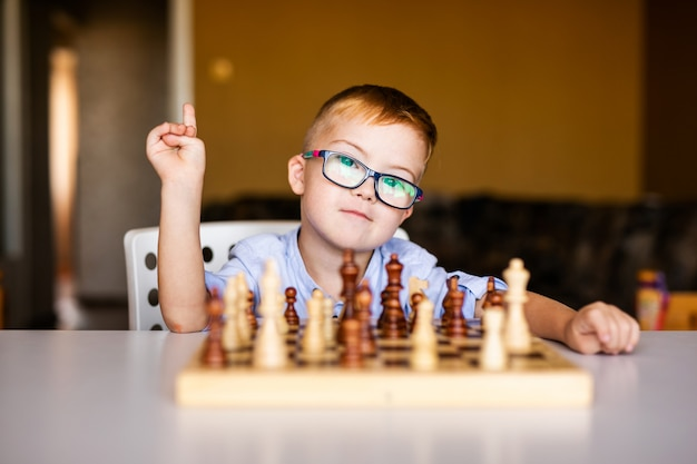 Маленький мальчик с синдромом дауна с большими синими очками играет в шахматы в детском саду