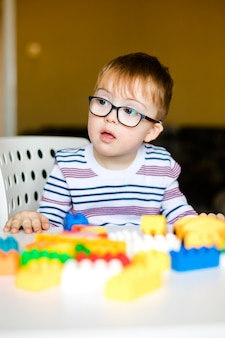 Little baby boy with down syndrome with big blue glasses playing with colorful bricks