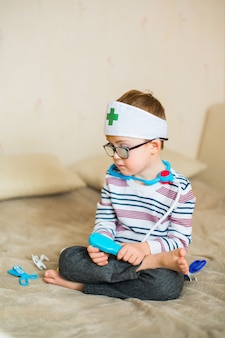 Little baby boy with down syndrome with big blue glasses playing with doctor toys