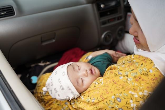 車の中でイスラム教徒のお母さんと一緒に旅行に行く小さな男の子