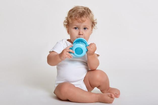 Маленький ребенок ребенок пьет из голубой бутылки