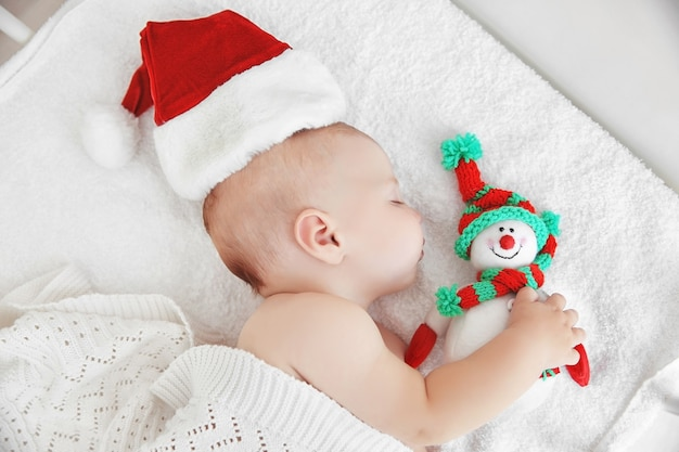 Little baby in christmas hat on white bed