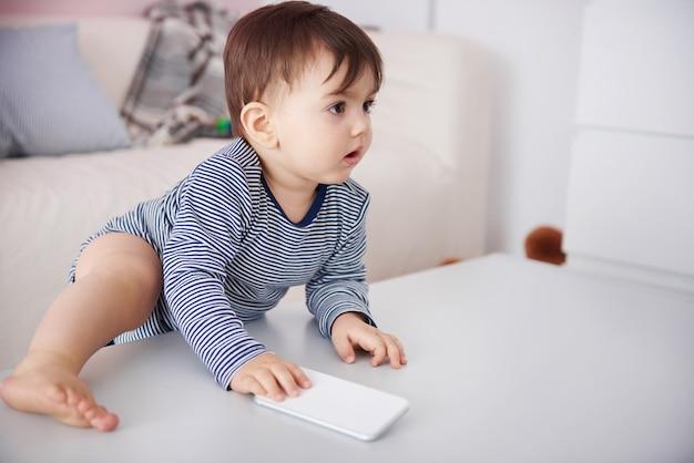 テーブルの上に携帯電話で登る小さな赤ちゃん