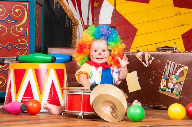 Маленький ребенок-клоун с красным носом в разноцветном парике с шариками.