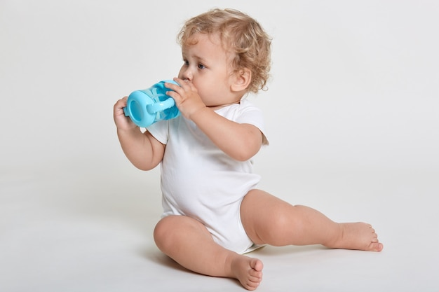 Little baby drinking water from blue bottle, looking aside while sitting on floor, posing barefoot and dresses bodysuit, cute infant kid having wavy blond hair.