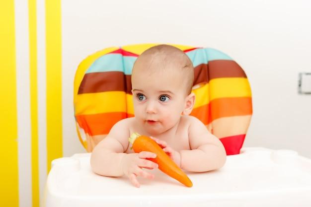 Маленький ребенок ест морковь