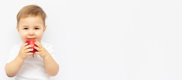 Маленький ребенок ест яблоко, портрет крупным планом, концепция здравоохранения здорового питания ребенка