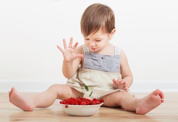 Маленький ребенок ест ягоды