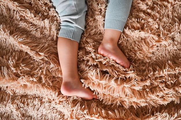 ふわふわのチェック柄の表面に小さな赤ちゃんの足。