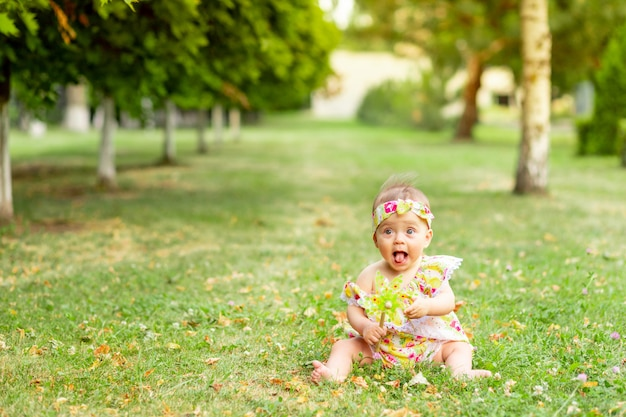 Little baby girl 7 months old sitting on a green lawn in a yellow dress and playing with a toy, walking in the fresh air, space for text
