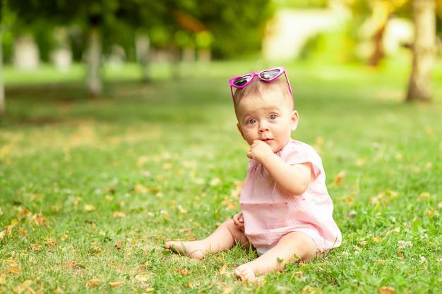 Маленькая девочка 7 месяцев сидит на зеленой траве в розовом боди и ярких очках, гуляет на свежем воздухе