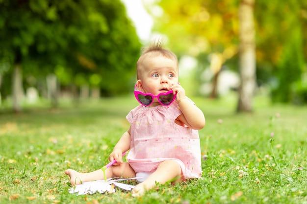 Маленькая девочка 7 месяцев сидит на зеленой траве в розовом боди и ярких очках