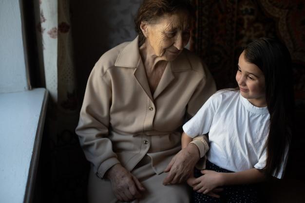 小さな女の赤ちゃんと非常に老婆。祖母を抱き締める小さな子供。孫娘