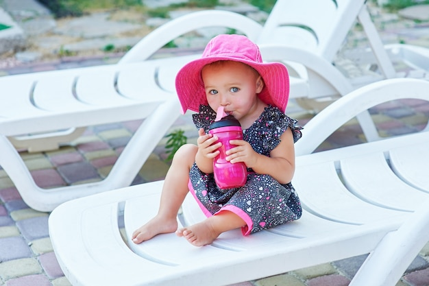 Little baby girl in autumn park drinks from pink plastic bottle