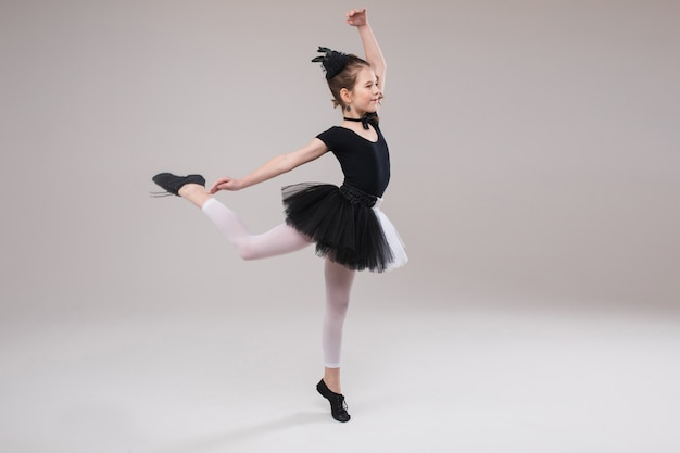 Little baby girl ballerina dancing in black and white clothing smiling having positive emotion