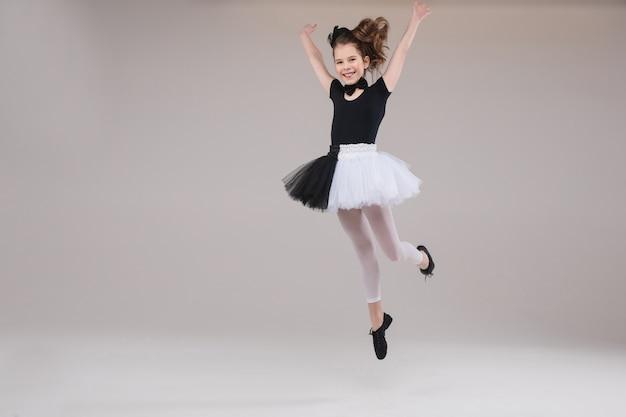 肯定的な感情を持っている笑顔の黒と白の服で踊る小さな女の赤ちゃんバレリーナ