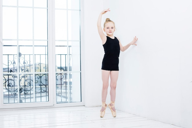 Little baby girl ballet dancer doing stretching in bright room on happy and cute