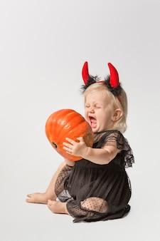 Little baby girl in black dress and devil horns
