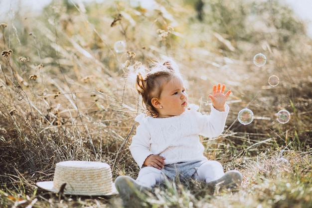 Little baby girl blowing soap bubbles in field