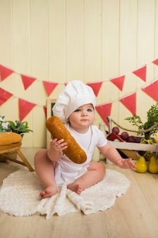 Little baby girl in a chef costume sits holding bread