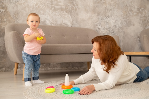 Little baby girl collects a pyramid with grandparents at living room. grandmother plays with granddaughter on the floor