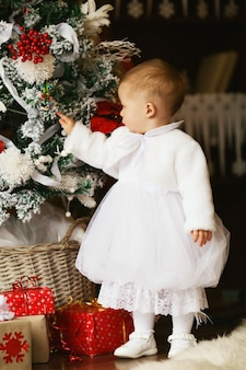 小さな女の赤ちゃんがクリスマスツリーを飾る