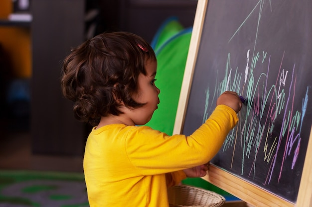 A little  baby girl draws on a blackboard with colored crayons