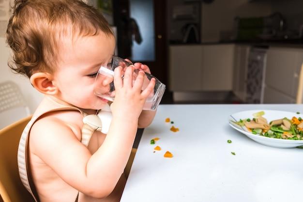 Маленькая девочка пьет воду из стеклянной чашки, сидя на ее высоком стуле во время обеда.