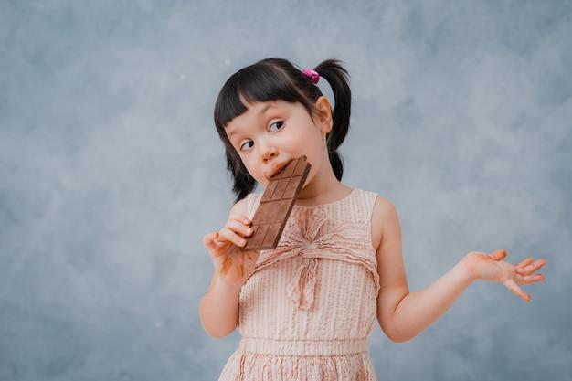 작은 여자 아기는 초콜릿을 먹고 회색 파란색 스튜디오에 그녀의 손가락을 핥는