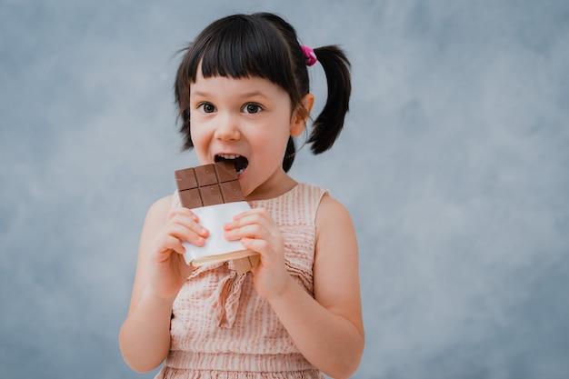 작은 아가 초콜릿을 먹고 회색 파랑에 그녀의 손가락을 핥는