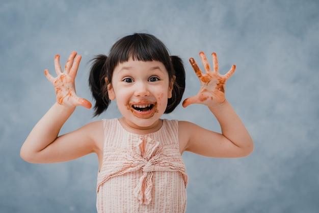 작은 아가 초콜릿을 먹고 그녀의 손가락을 핥는
