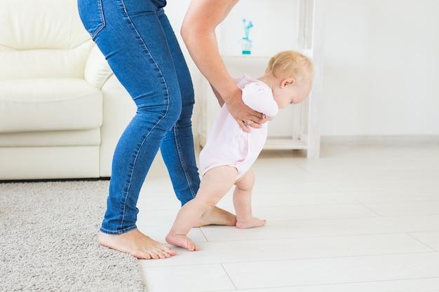 小さな女の赤ちゃんはお母さんの助けを借りて最初の一歩