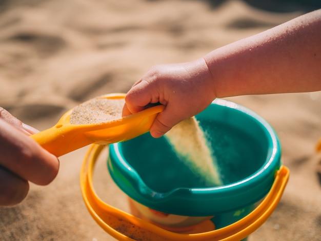 화창한 여름날 양동이를 들고 모래 해변에서 즐겁게 노는 어린 소녀
