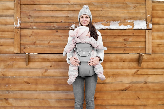 Little baby girl and her mother babywearing in the ergo carrier in winter wooden background