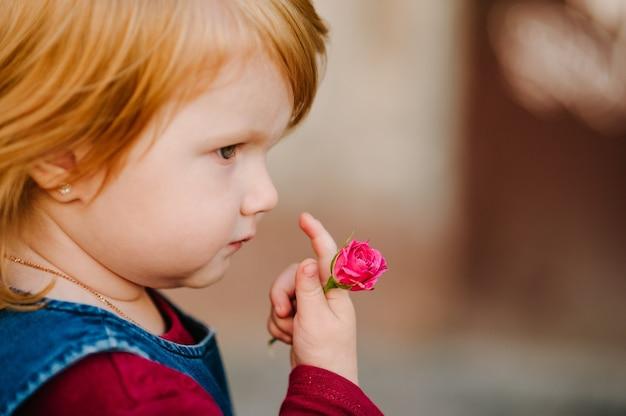 아기 소녀 야외에서 그녀의 손에 장미 꽃을 보유하고있다. 아이가 꽃을줍니다. 행복한 가족의 개념.