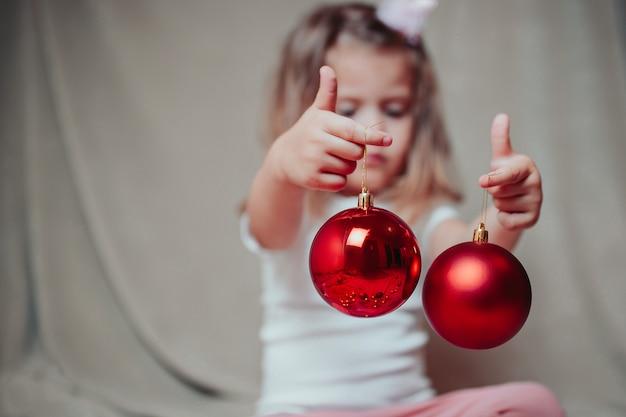 Little baby girl holds red christmas balls.