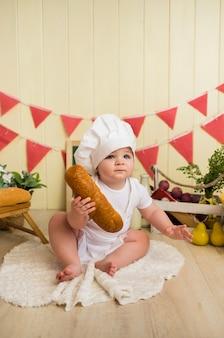 シェフの衣装を着た小さな女の赤ちゃんがパンを持って座っています