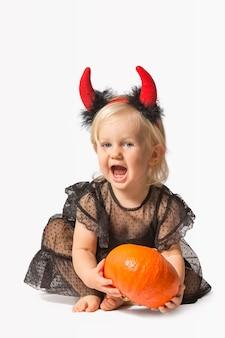 黒のドレスと悪魔の角の小さな女の赤ちゃん