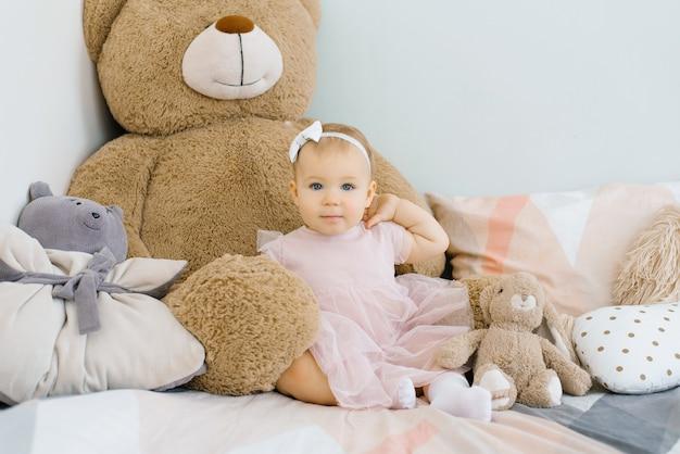 大きなテディベアともっとふわふわのおもちゃに囲まれたベッドに座っているピンクの服を着た小さな女の赤ちゃん
