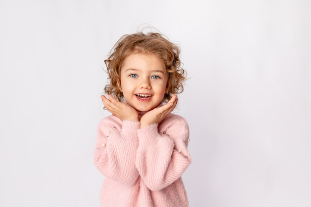 Маленькая девочка в розовой зимней одежде на белом фоне радуется, место для текста