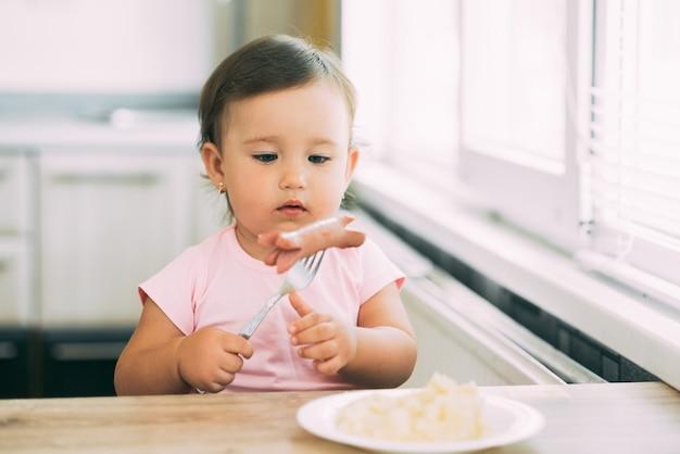 소시지와 으깬 감자를 먹고 부엌에서 아기 소녀
