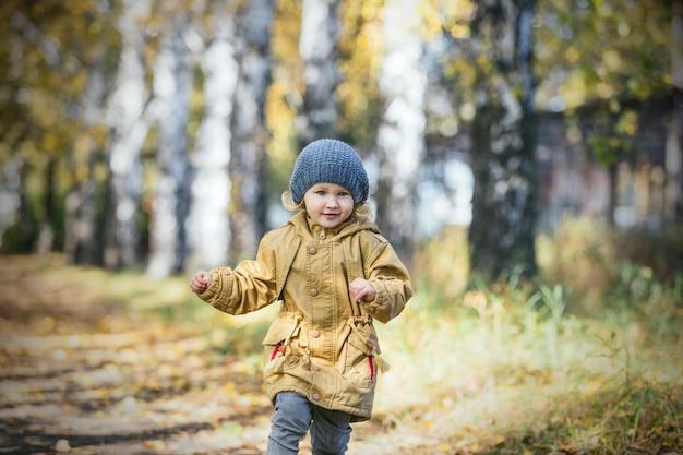 공원에서 가을 따뜻한 재킷과 모자에 작은 아기 소녀
